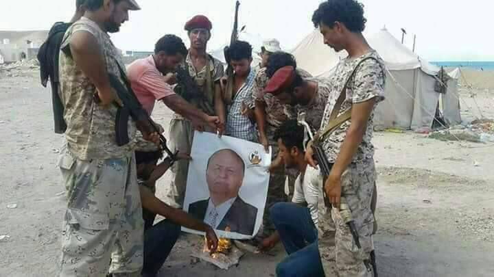 """ردا على دهس صور """"ابن زايد"""".. الإمارات تأمر مرتزقتها باحراق صور الرئيس """"هادي"""" في عدن"""